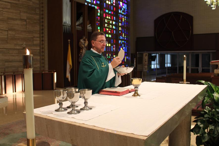 Padre consagrando a Eucaristia