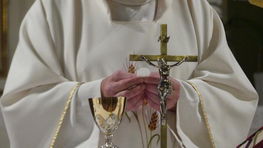 Padre na missa, com a Eucaristia nas mãos